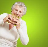 Portrait of senior woman eating vegetal sandwich over green back — Stock Photo