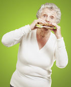 Senior woman eating a healthy sandwich against a green backgroun — Stock Photo