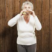 Sênior mulher comendo um sanduíche saudável contra um de madeira backgrou — Foto Stock