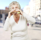 Senior woman eating a healthy sandwich against a street backgrou — Stock Photo