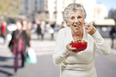 Senior woman eating cereals out of a red bowl against a street b — Stock Photo