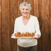 Portrait of senior woman showing homemade muffins against a wood — Stock Photo