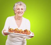 Portrait of senior woman showing a chocolate muffin tray over gr — Stock Photo
