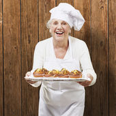 Senior woman cook holding a tray with muffins against a wooden b — Foto de Stock