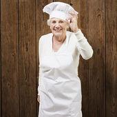Äldre kvinna kock gör en utmärkt symbol mot trä bac — Stockfoto