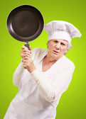 Cook senior woman angry trying to hit with pan over green backgr — Stock Photo