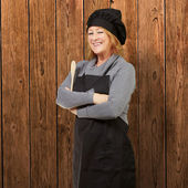 Portrait of woman cook wearing apron against a wooden wall — Stock Photo
