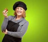 Portrait of middle aged cook woman holding a delicious homemade — Stock Photo
