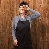 средний возрасте женщина кук, глядя через пончик против деревянный — Стоковое фото