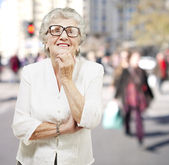 Portrait of senior woman thinking and looking up at a crowded pl — Stock Photo