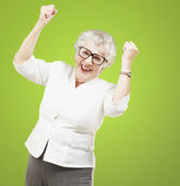 Portrait of a cheerful senior woman gesturing victory over green — Stock Photo