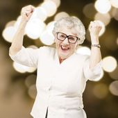 Portrait of a cheerful senior woman gesturing victory against a — Stock Photo