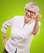 Portrait of adorable senior woman doing good gesture over green — 图库照片