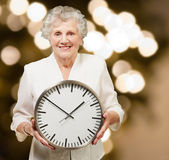 Portrait of a happy senior woman holding clock against a abstrac — Stock Photo