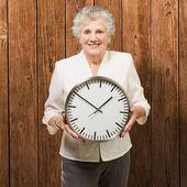 Ritratto di un orologio di detenzione donna felice senior contro un legno — Foto Stock