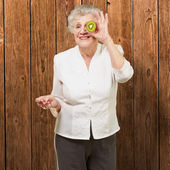 Portrait of senior woman holding kiwi in front of her eye agains — Stock Photo