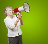 Portrait of senior woman holding megaphone over green background — Stock Photo