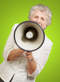 Portrait of senior woman screaming with megaphone over green bac — Stock Photo
