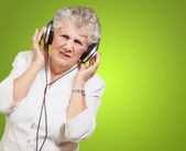 Portrait of senior woman listening to music over green backgroun — Stock Photo