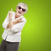 Portrait of senior woman doing rock symbol over green background — Stock Photo