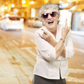 Portrait of senior woman doing rock symbol against a city night — Stock Photo