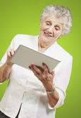 Portrait of senior woman touching digital tablet over green back — Stock Photo
