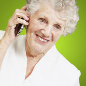 Portrait of senior woman talking on mobile over green background — Stock Photo