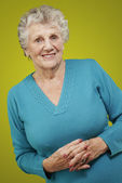 Portrait of senior woman standing over yellow background — 图库照片