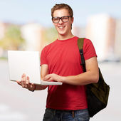 Portrait of young man holding laptop and wearing backpack at cit — Stock fotografie
