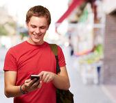 通りで携帯電話の画面に触れる若い男の肖像 — ストック写真