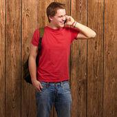 Retrato de jovem homem falando no celular contra uma parede de madeira — Foto Stock