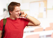 Portrait of young man talking on mobile at classroom — Stock Photo