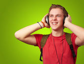 Portrait of cheerful young student listening music with headphon — Stockfoto