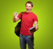 Young angry student man roughing a sheet over green background — 图库照片