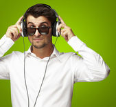 Portrait of young man listening to music using headphones over g — Stock Photo