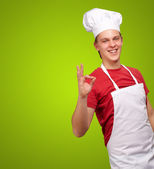 Portrait of young cook man doing success symbol over green backg — Stock Photo