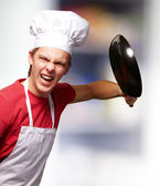 Portrait of angry young cook man hitting with pan indoor — Stock Photo