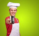 Metal teneke üzerinde yeşil ba tutan genç aşçı adam portresi — Stok fotoğraf