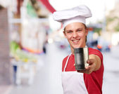 Portrait of young cook man holding a metal tin can at street — Stock Photo