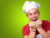 Portrait of young cook man screaming over green background — Stock Photo