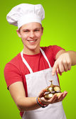 Portrait of young cook man pressing a golden bell over green bac — Stockfoto