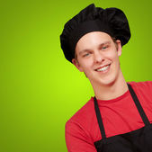 Portrait of young cook man wearing uniform and smiling over gree — Stock Photo