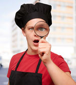Portrait of young cook man looking through a magnifying glass ag — Stock Photo