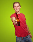 Portrait of young man holding beer against a green background — 图库照片