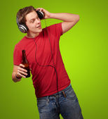 Portrait of young man listening music and holding beer on green — Stock Photo