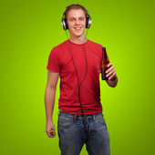 Portrait of young man listening music and holding beer over gree — Stock Photo