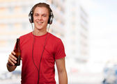 Portrait of young man listening music and holding beer against a — Foto Stock