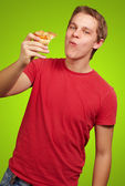 Portrait of young man eating pizza portion over green backgorund — Stock Photo