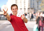 Portrait of young man doing a victory gesture playing poker at c — Stock Photo