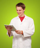 Portrait of young academic holding a digital tablet over green b — Stock Photo